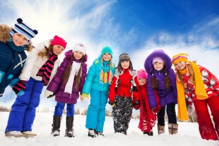 bending down: Gran grupo de los ni�os, los ni�os y ni�as de 5-10 a�os de edad doblado hacia abajo, de la mano, de pie juntos en una fila