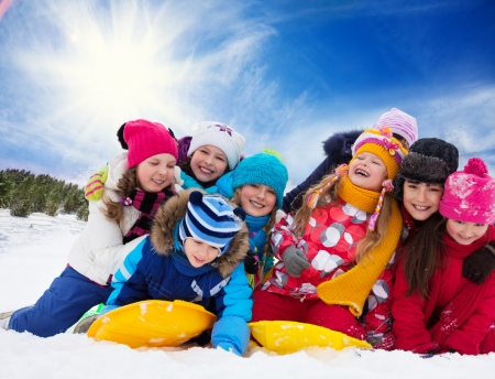 diversity children: Large group of kids playing together in snow on sunny day