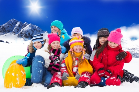 Large group of diversity looking kids 5-10 years old boys and girls on snow day in mountains photo