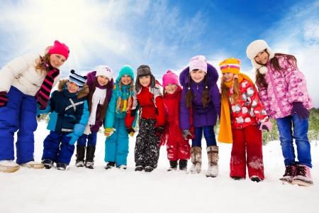 bending down: Gran grupo de los ni�os, los ni�os y ni�as de 5-10 a�os de edad inclin�ndose a la c�mara, de la mano, de pie juntos en una fila
