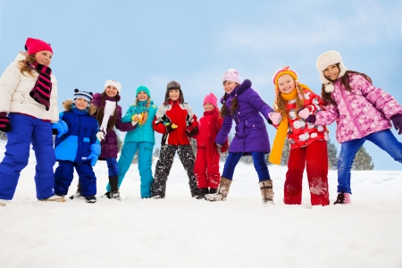 Group of happy kids, having fun on snow day, holding hands and walking in circle photo
