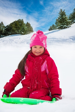 sledding: Happy, smiling girl sitting on sled, on slide in the forest