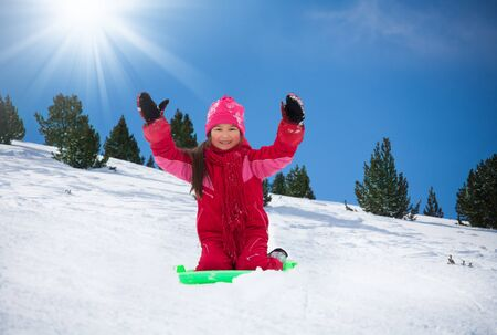 hands lifted: Happy, smiling girl sitting on sled with her hands lifted, on slide in the forest Stock Photo
