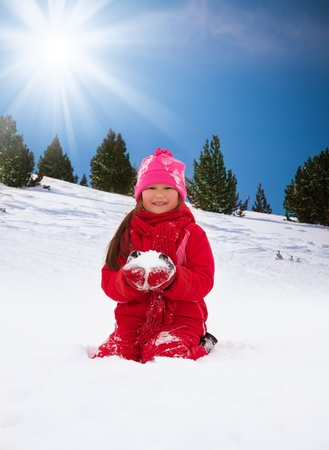 Little happy smiling girl about to throw snowball in the air photo