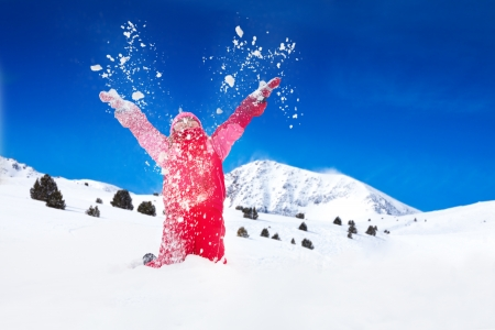 snow woman: Little happy smiling girl  throws snow in the air with snowflakes flying in all directions Stock Photo