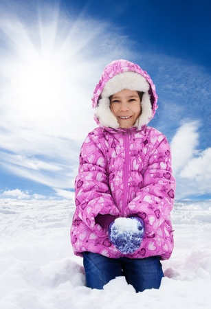 Little happy smiling girl about to throw snowball in the air on winter day photo