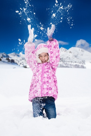 Little happy smiling girl in pink throws snowin the air with snawflakes flying in all directions photo