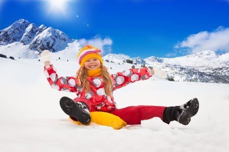 sledding: Happy, smiling girl sitting on sled with her hands lifted, with mountains on mountains Stock Photo
