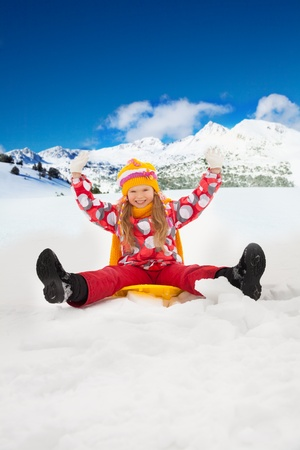 6 years: Smiling, smiling girl sitting on sled with her hands lifted, in the mountains