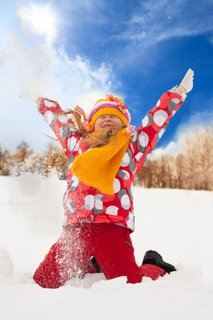 Happy supper exited girl throwing snow in the air on sunny day photo