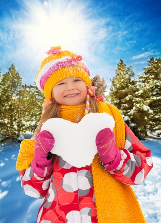 Little happy girl hold heart made of snow in yellow scarf and bright hat photo