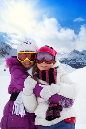 Two cute kids girls hugging together with mountain on background photo