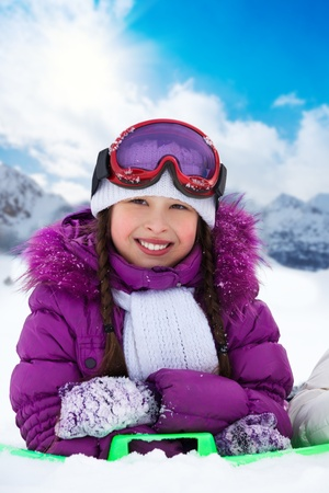 Happy smiling10 years old girl laying in snow in snowboard glasses photo