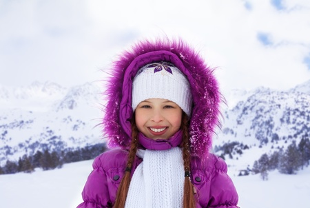 Cute smiling Caucasian girl in purple coat on snowy winter day photo
