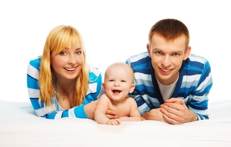 Cute little baby boy laughing laying with parents in the bed photo
