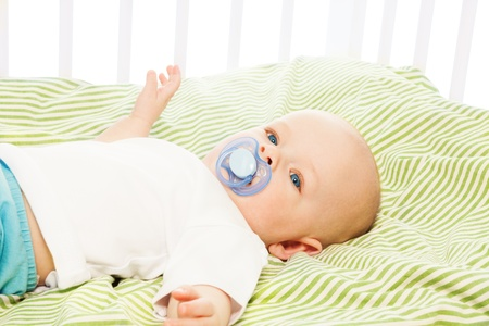 soother: Calm little 6 month boy laying in his crib with pacifier