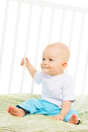 6 month old: Close up portrait of happy 6 month old boy sitting smiling in his crib Stock Photo