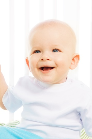 6 month old: Close up portrait of happy 6 month old boy laughing in his crib