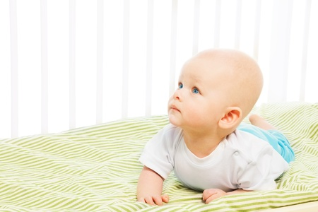Little baby boy learning to crawl in his crib, isolated on white photo