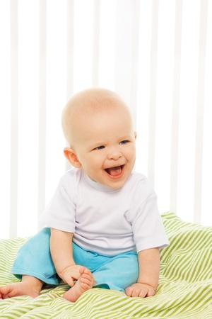Baby boy laugh, sitting in his crib with photo