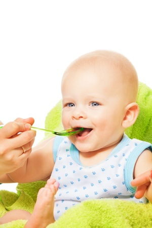 Cute little boy eats from the spoon with mothers help photo