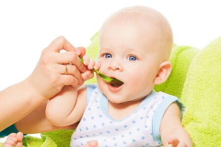 Teaching cute little baby boy to eat from the spoon photo