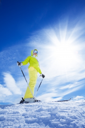 ski mask: Happy young woman skier stand on top of the mountain on bright sunny day