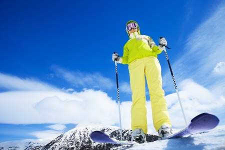 Happy young woman skier stand on top of the mountain and ready to go downhill - wide angle shoot with copy space photo
