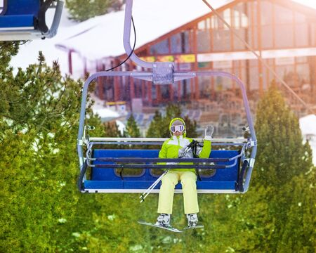 Yong happy woman sitting in ski lift chair and waiving her hand photo