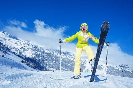 off piste: Yong happy woman shows her ski, standing on the mountain slope