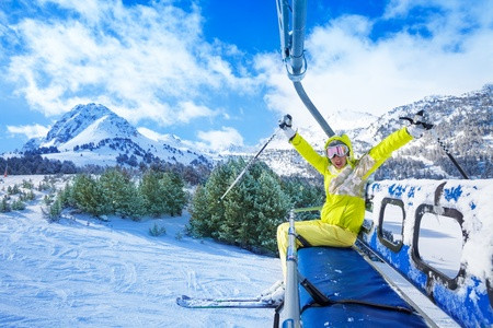 lifted: Happy young woman sitting on the ski lift chair with lifted hands and smile with mountains on background Stock Photo