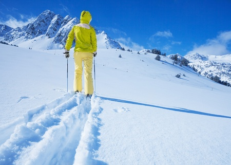 concur: One man walking with ski over the snow land to the mountain view from back