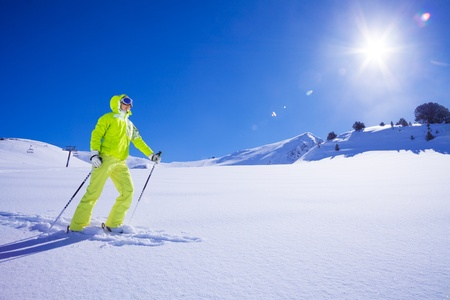 concur: Young skier in bright clothes the first one to concur new snow terrain