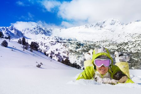 ski goggles: Young smiling woman in ski glasses laying in snow with mountain on background