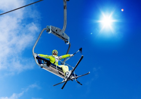 Happy skier young woman sit on the ski lift and waiving hand with sky on background photo