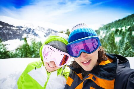 Young couple of skiers with mountains on background photo
