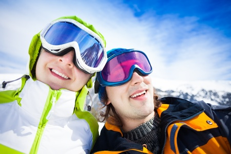Young couple of snowboarders with mountains on background photo