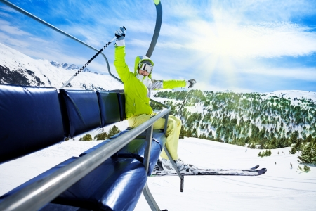 ropeway: Happy young woman skier on ski lift with smile and lifted happy hands Stock Photo