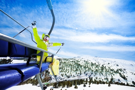 cheerfully: Happy young woman skier sit on ski lift chair, smiling and cheerfully lifting her hands