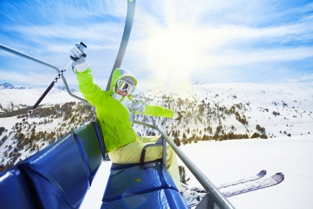 ski slopes: Happy young woman skier sitting on ski lift chair, smiling and happily lifting her hands Stock Photo