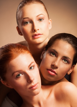 Vertical portrait of three woman with different appearance - blond, red, and Latino photo