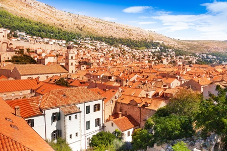 Red tile roofs of old Dubrovnik city with mountains on background photo