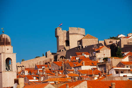 Main tower of Dubrovnik fort walls with town roofs on foreground photo