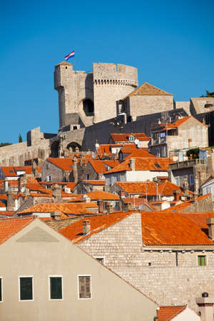 Main tower of Dubrovnik fort walls with houses red roofs photo