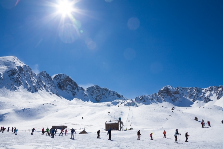 背景に高山のピークの斜面を滑るスキーヤーの多く