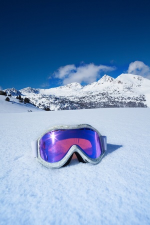 Ski and snowboard mask in the snow with mountains on background
