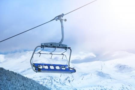 背景の山のてっぺんでスキー場のリフトの椅子のクローズ アップ。