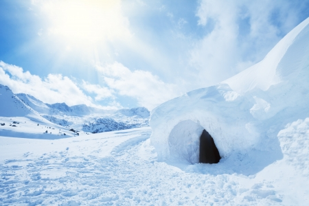survive: igloo and snow shelter in high snowdrift with mountains peaks on background Stock Photo