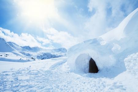 überleben: Iglu und Schnee sch�tzen in hohen Schneewehe mit Berggipfel im Hintergrund