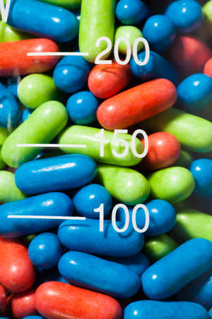 Close-up of color drug pills in the transparent glass container photo